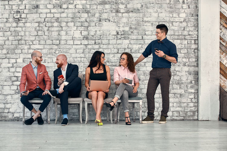 Full length of friends sitting against wall