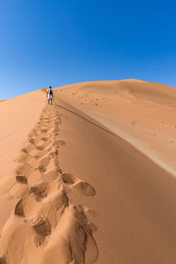 Woman walking on desert against clear sky