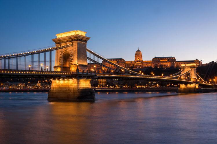 Illuminated chain bridge over danube river in city at night