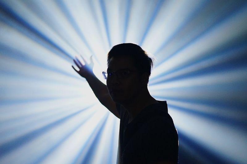 Portrait of man standing against light beams