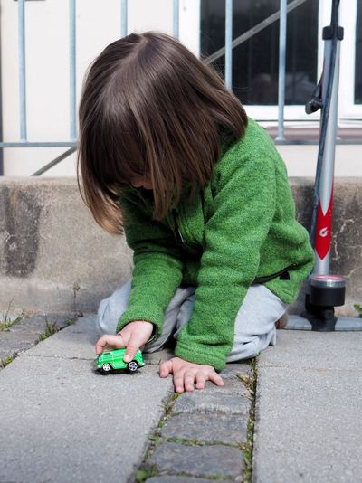 Childhood Child One Person Casual Clothing Playing Day Full Length Lifestyles Leisure Activity Green Color Men Boys Males  Girls Real People Offspring Innocence Outdoors Warm Clothing Girl Green Color Green Car Bus Cars Play Backyard Yard Cobblestone Cobbled Fleece