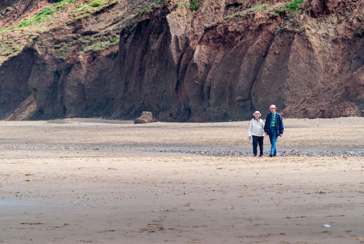 Men walking on rocks by land