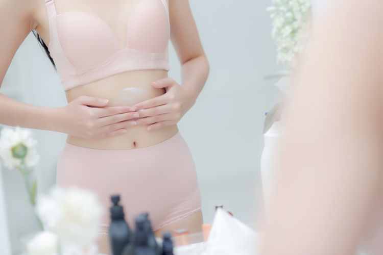 Midsection of woman holding white while standing at home