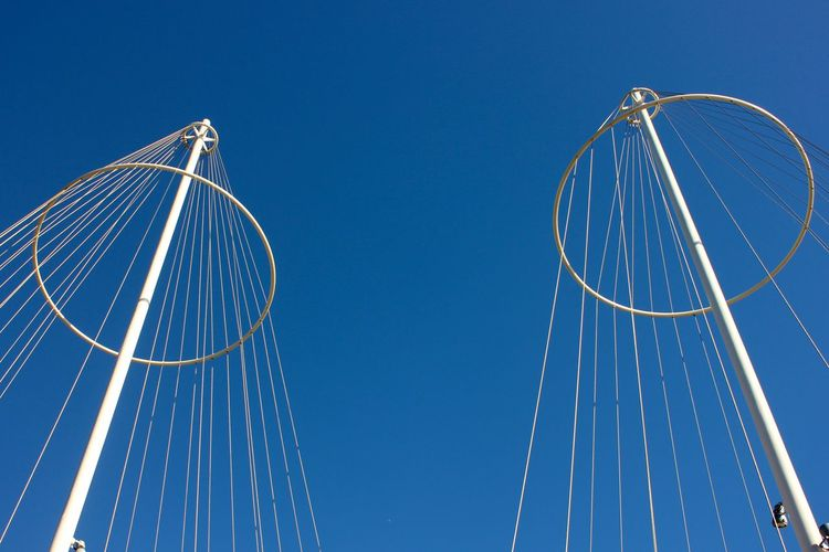 Low angle view of suspension bridge against clear blue sky