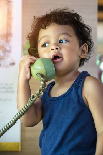 Cute boy talking on telephone at home