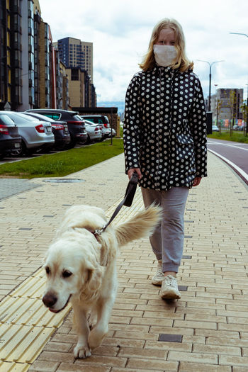Rear view of woman with dog walking on sidewalk in city