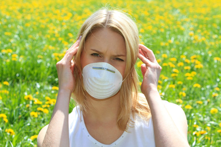 young woman protects herself with a respiratory mask against pollen allergy Woman Adult Allergy Blond Hair Flower Front View Girl Headshot Illness Lifestyles Mask Nature One Person Outdoors Painful People Pollen Pollen Allergy Portrait Protection Respiratory Mask Sick Sickness Spring Time Summer