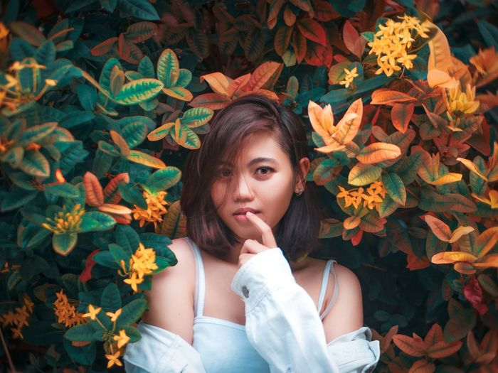 Portrait of a beautiful young woman with autumn leaves