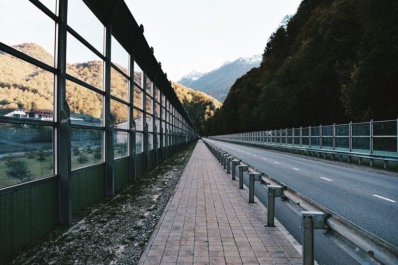 Sidewalk leading towards mountains against clear sky
