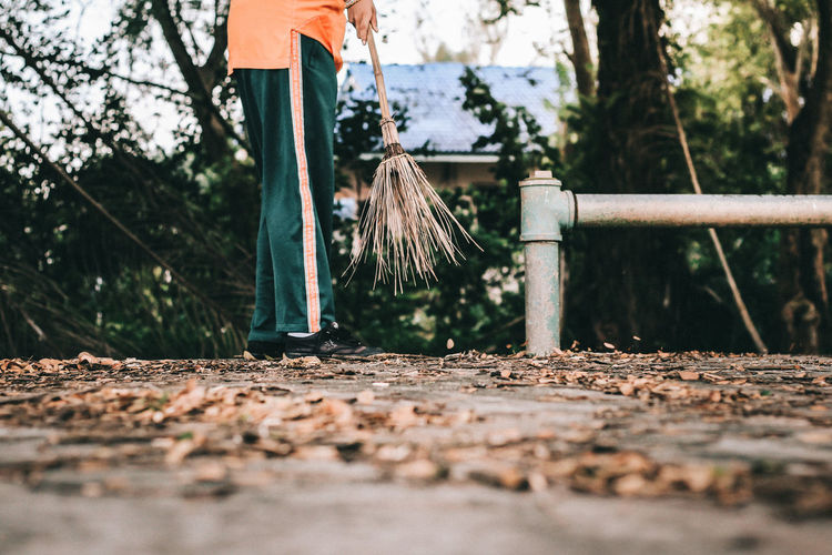 Low section of man with broom standing on leaves covered footpath