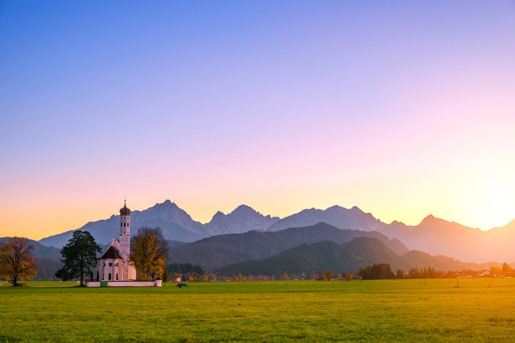 Scenic view of church on landscape against clear sky during sunset