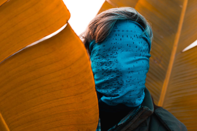 Close-up of man face covered with blue scarf standing amid leaves