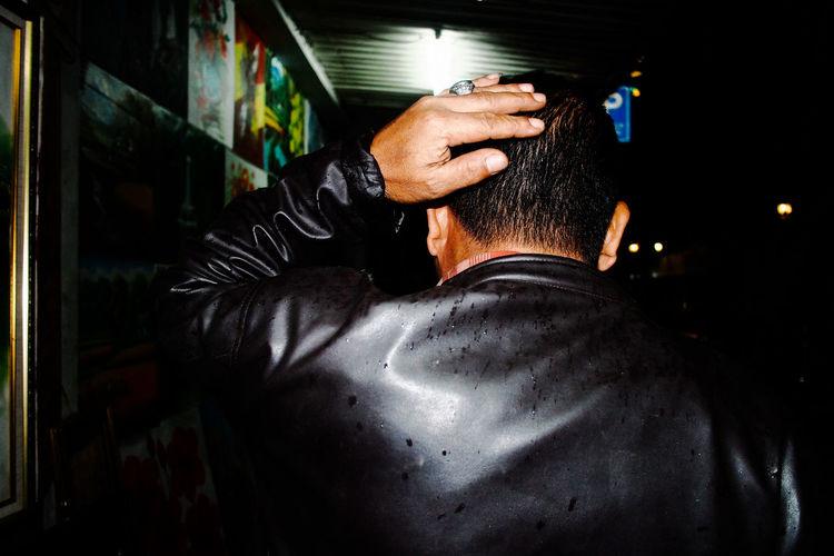 Rear View Of Man Wearing Leather Jacket Walking On Street At Night