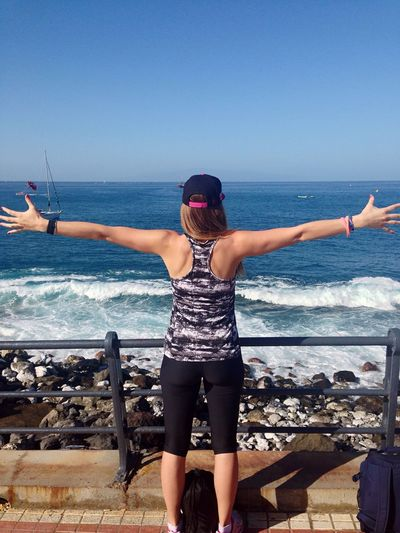 Rear view of woman with arms outstretched against sea