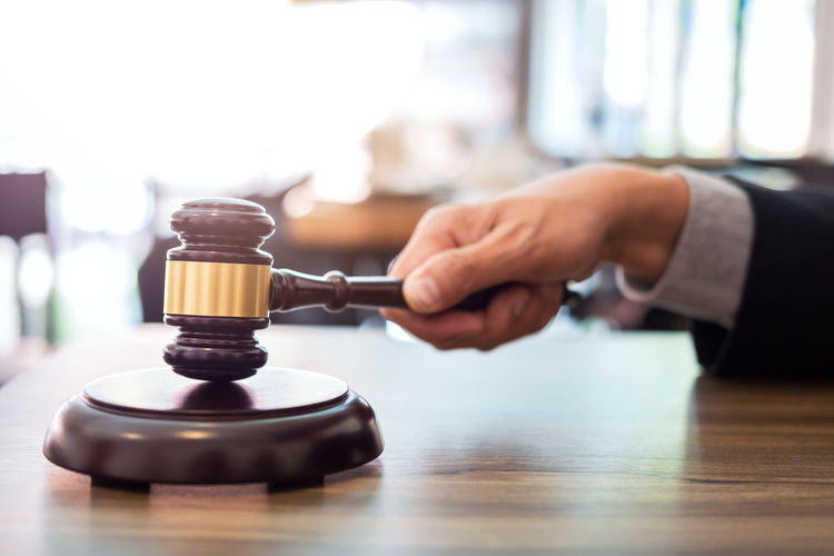 Cropped Hand Of Lawyer Holding Gavel On Desk In Office