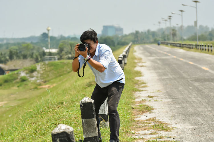 Full length of man photographing while standing on road