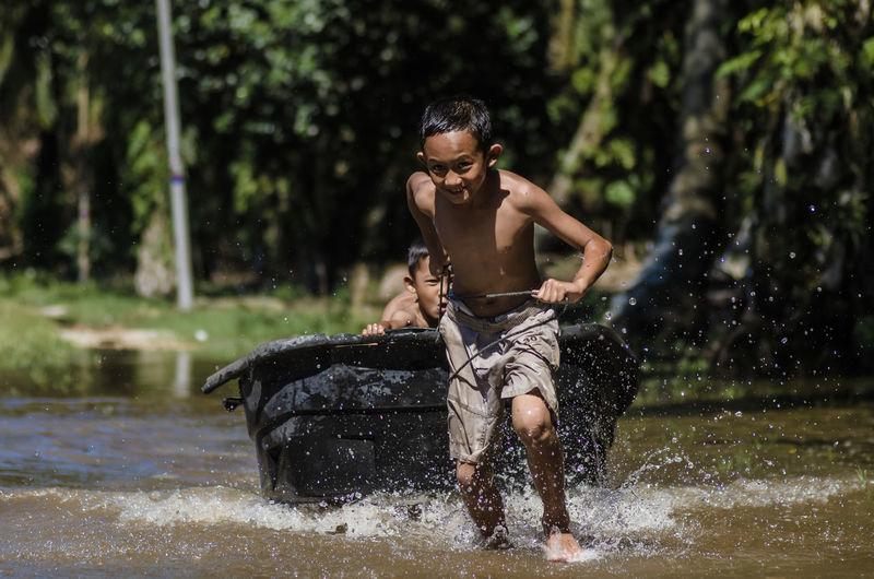 Shirtless boys splashing water while playing in lake