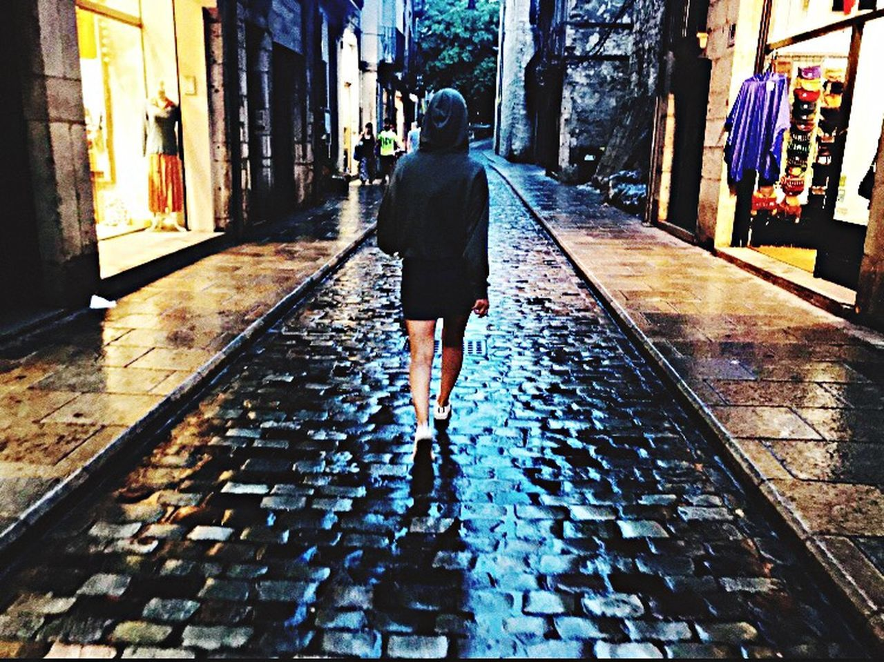 rear view, one person, architecture, full length, real people, building exterior, built structure, walking, city, lifestyles, direction, women, day, the way forward, building, leisure activity, adult, street, wet, outdoors, rain, rainy season, alley