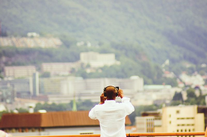 Rear view of woman photographing against cityscape