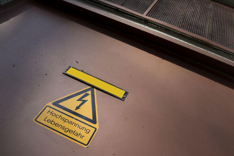 High angle view of warning sign on walkway