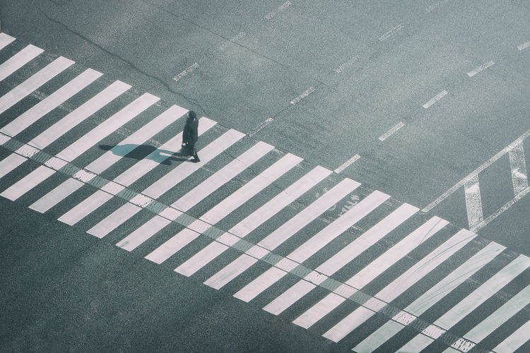 High Angle View Of Man Walking On Zebra Crossing