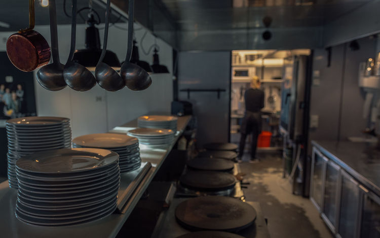 Café kitchen scene with plates and spoons hanging down Crêperie Crêpes Commercial Kitchen Day Food And Drink Food And Drink Establishment Indoors  One Person Plates Real People Spoons