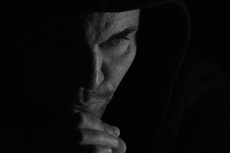Close-Up Of Thoughtful Mid Adult Man With Hand On Chin Against Black Background