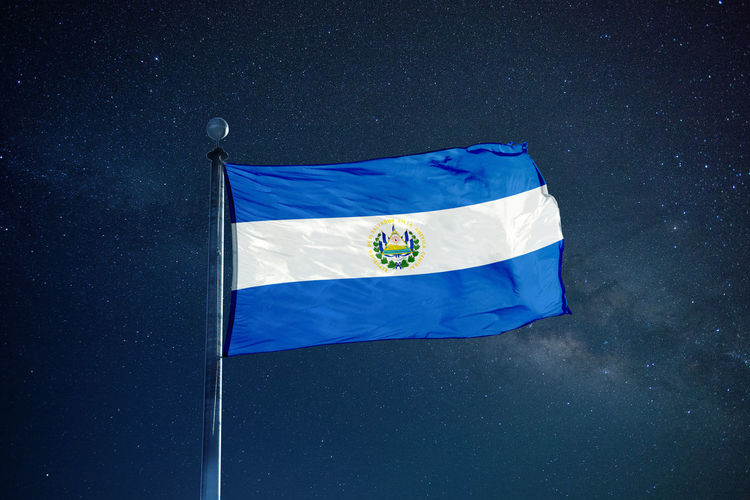 Low angle view of el salvadoran flag against star field sky