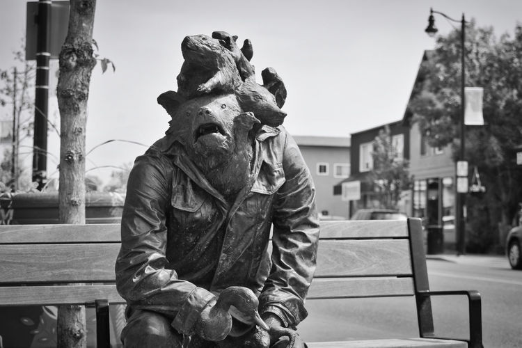 Statue of man sitting on bench