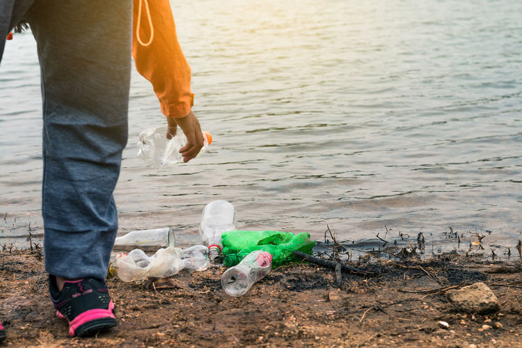 Low section of volunteer holding plastic bottle by lake
