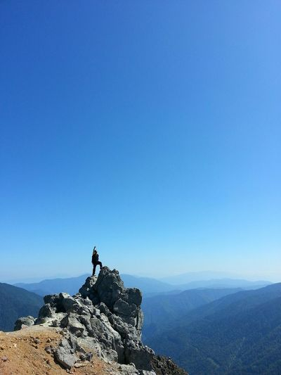 Man Standing On Mountain Peak Against Clear Blue Sky