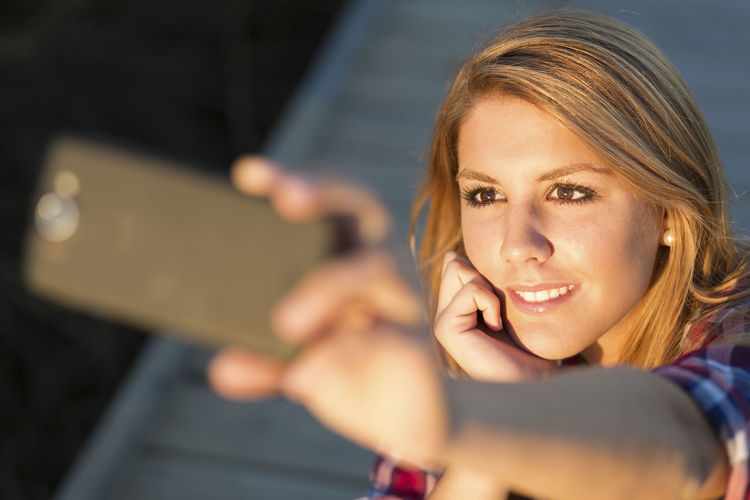 High angle view of young woman taking selfie with smart phone