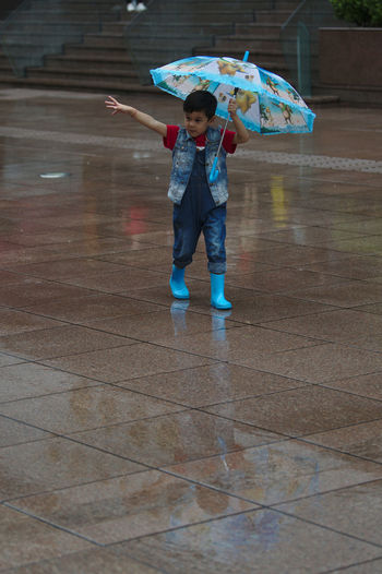 Fun Nanjing Road Rainy Days Shanghai Streets Blue Boots Boys Childhood Full Length Leisure Activity Lifestyles One Person Outdoors Protection Rain Real People Street Photography Umbrella Weather