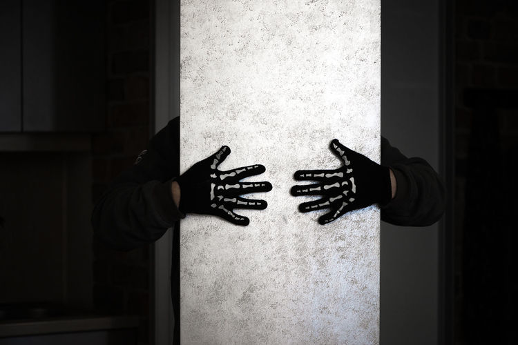 Cropped hands of man wearing glove on column