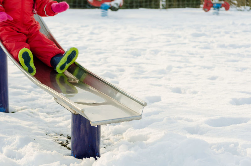 Low section of child on slide at snow covered playground