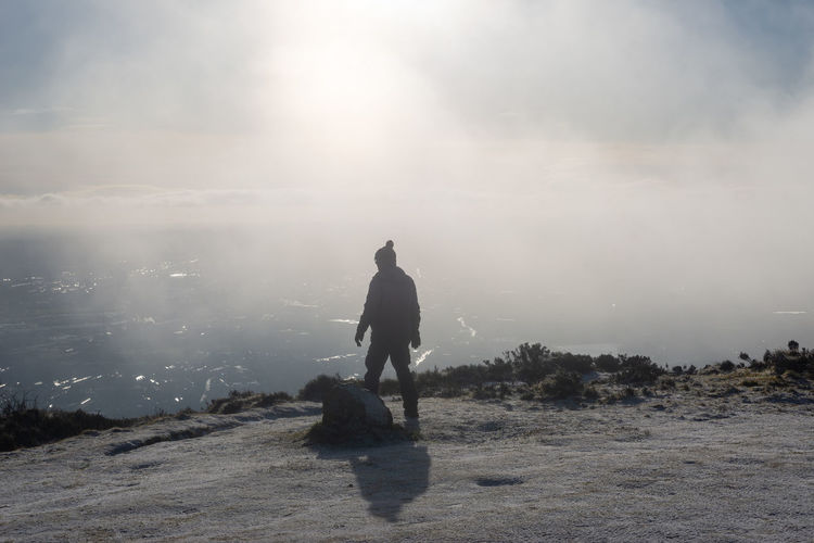 Rear view of man on land against sky