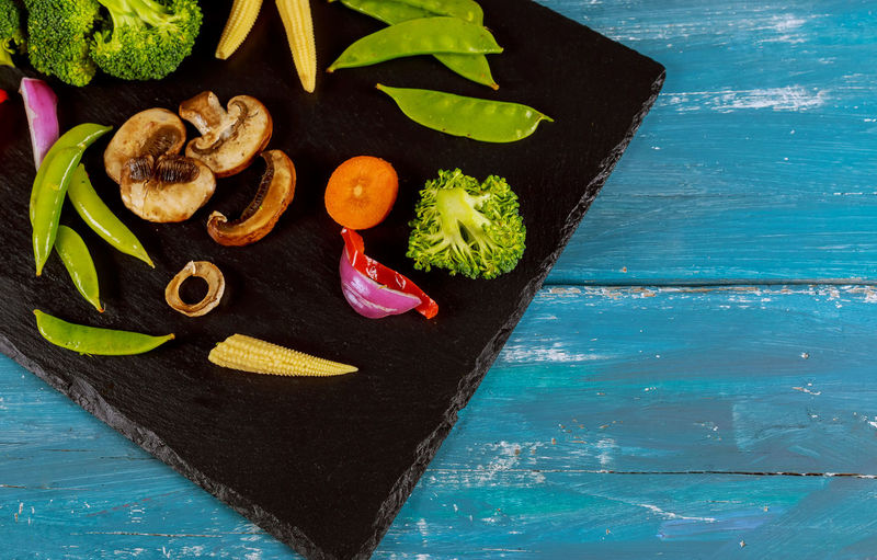 High angle view of vegetables on slate over wooden table