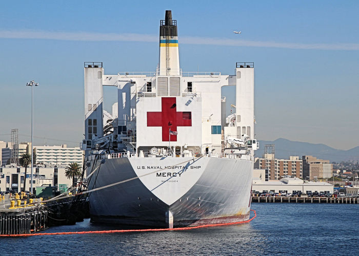 This is the third USNS Mercy (T-AH-19) which is the lead ship of her class of hospital ships in non-commissioned service with the United States Navy. Her sister ship is the USNS Comfort (T-AH-20). She was named for the virtue of compassion. In accordance with the Geneva Conventions, USNS Mercy and her crew do not carry any offensive weapons, though defensive weapons are available. Firing upon the Mercy would be considered a war crime. Mercy was built as an oil tanker, SS Worth, by National Steel and Shipbuilding Company, San Diego, in 1976. Starting in July 1984, she was renamed and converted to a hospital ship by the same company. Launched on 20 July 1985, USNS Mercy was placed in service on 8 November 1986. She has a raised forecastle, a transom stern, a bulbous bow, an extended deckhouse with a forward bridge, and a helicopter-landing deck with a flight control facility. The Mercy class hospital ships are the third largest ships in the U.S. Navy Fleet by length, surpassed only by the nuclear-powered Nimitz-class and Gerald R. Ford-class supercarriers. Hospital Ship, Mercy, Hospital, Medical, Disaster Relief, US Navy, Maritime, Mariner, San Diego, California, Architecture Building Exterior Built Structure City Commercial Dock Day Harbor Moored Nautical Vessel No People Outdoors Sailing Ship Sea Sky Transportation Water Waterfront