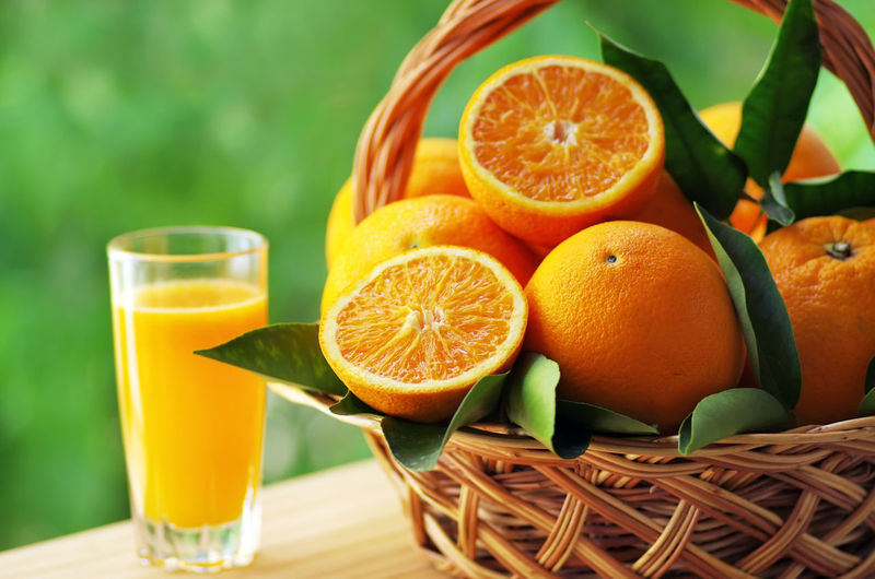 Close-up of oranges in basket by juice on table
