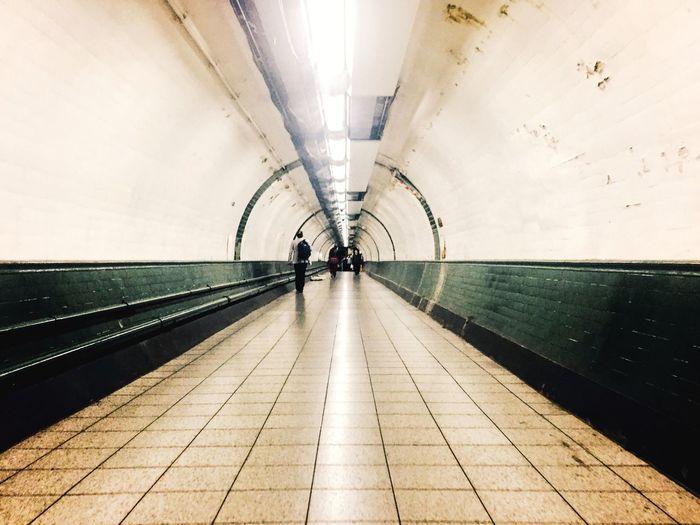 Man Walking In Illuminated Subway