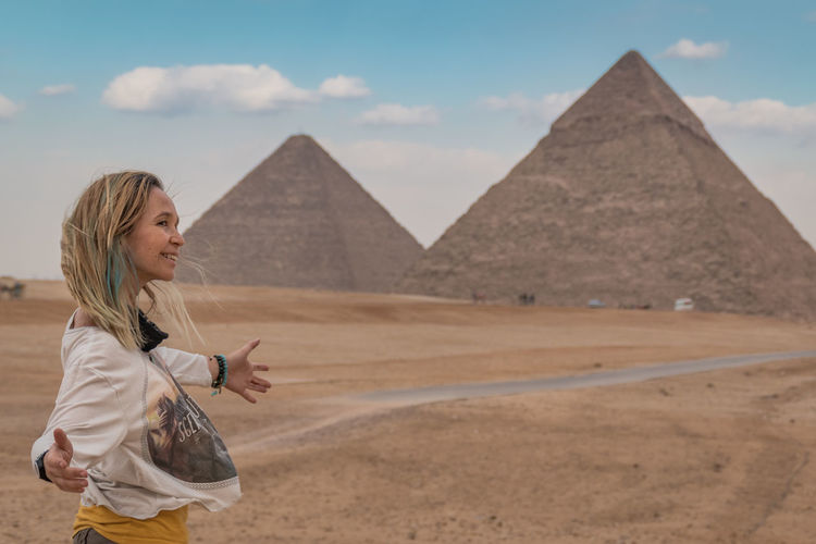 Woman looking away while standing against pyramids and sky