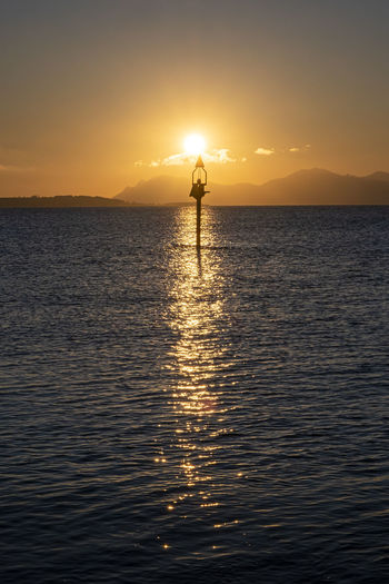 Silhouette person standing in sea against sky during sunset
