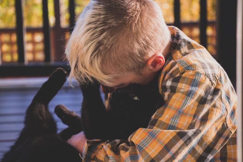 Side view of boy embracing cat at home