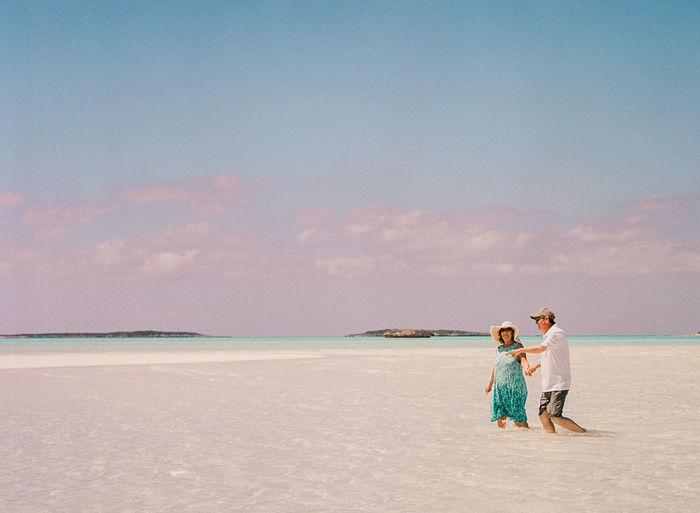 Couple walking in sea against sky
