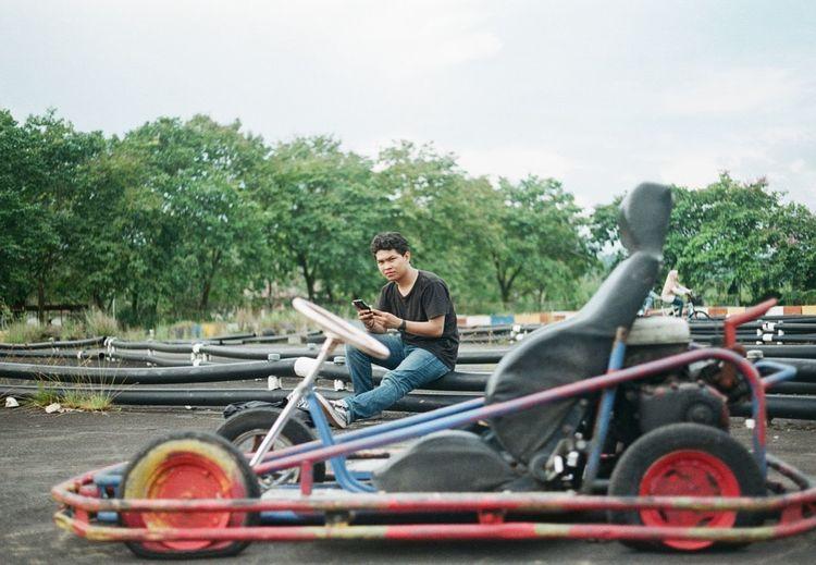 Portrait of man sitting by sports car on sports track