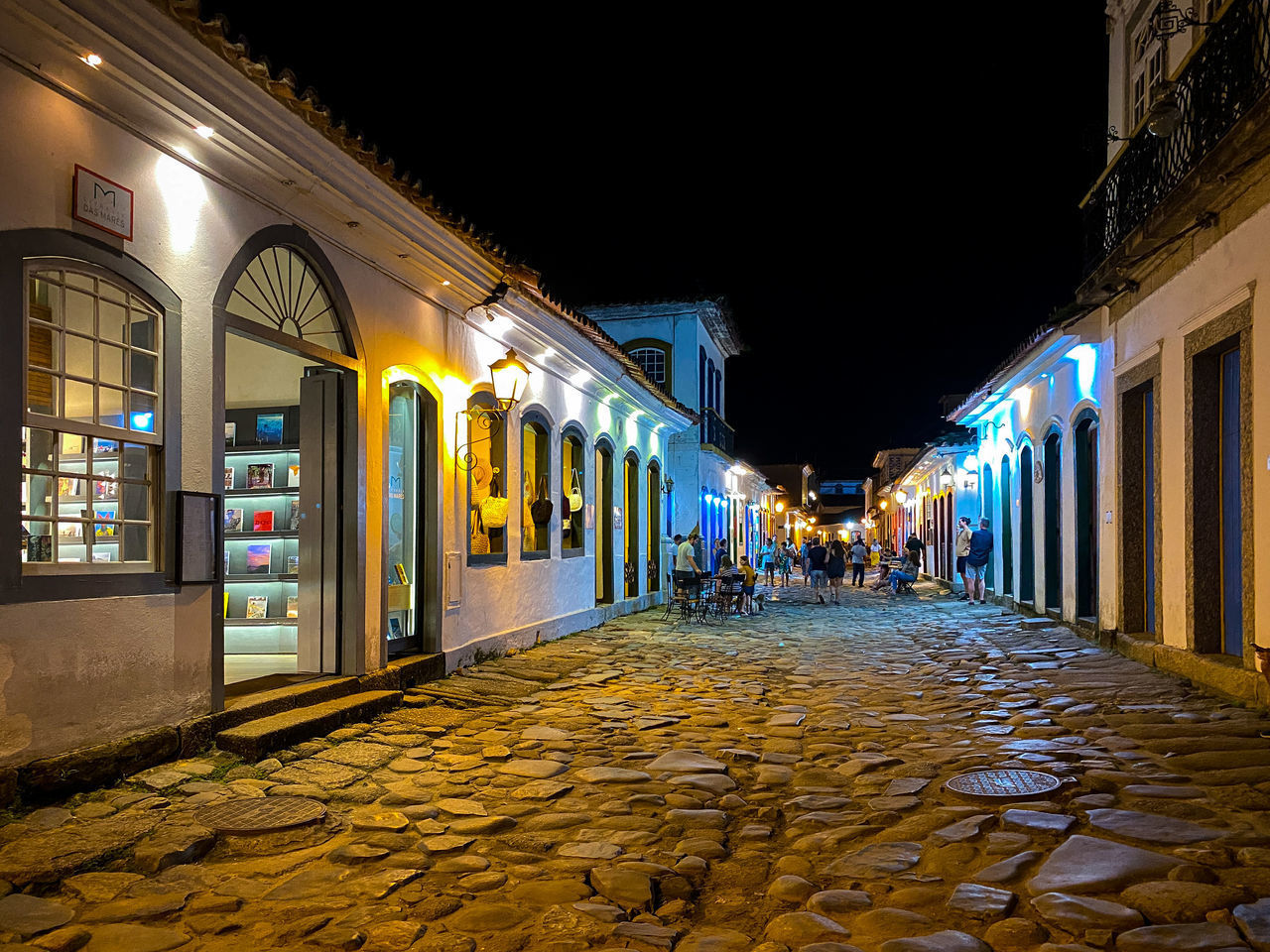 STREET AMIDST ILLUMINATED BUILDINGS AT NIGHT