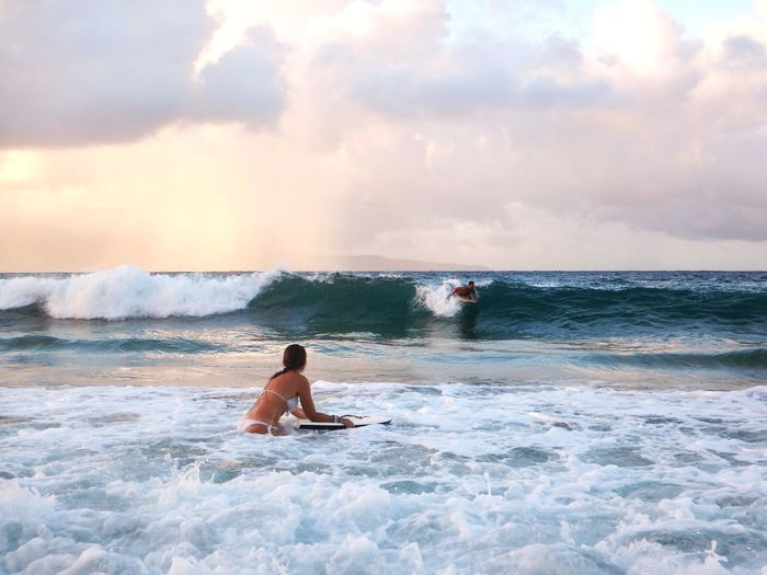 People Surfing In Sea Against Sky