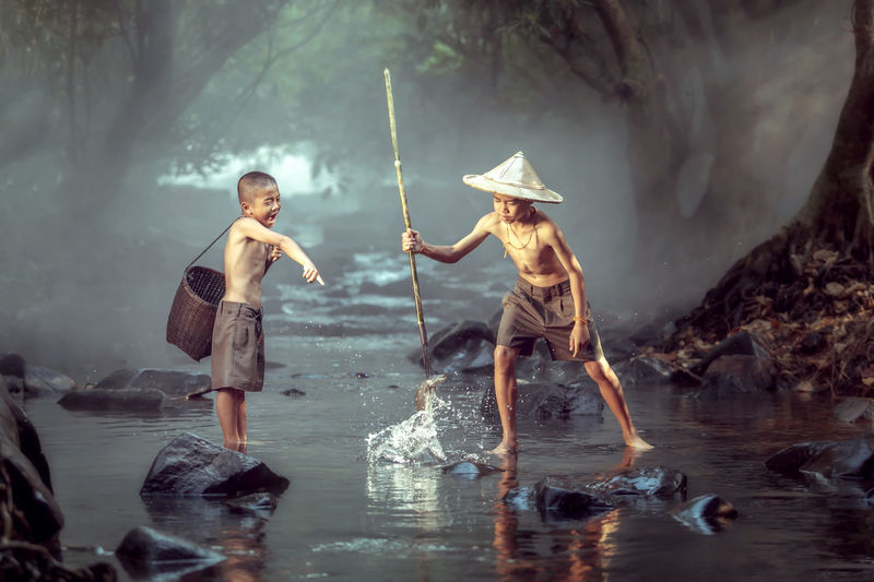 Two boys are happily having fun. To catch fish in the streams and stunning natural light in the background. And this is the way of life of children in the Northeast of Thailand. Couple Friendship, Animal Themes Childhood Day Fisherman Full Length Instagram Lake Love, Mammal Nature Nature, Pure, Asia, Vietnam , Tropical, Farm, Plant, Orchid, Flower, Beautiful, Blossom, Blooming, Leaf, Purple, Sunlight, Wallpaper, Closeup, Floral, Stem, Buds, Botany, Macro, Branch, Bright Outdoors People People Photography Real People Rural Scene Sakonnakhon Siam Standing Thailand, Two People Water Young Men first eyeem photo