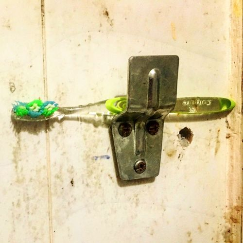 A monk's toothbrush Bathroom Tiles Toothbrush No People Metal Wall - Building Feature Close-up Green Color Day Built Structure Still Life Indoors
