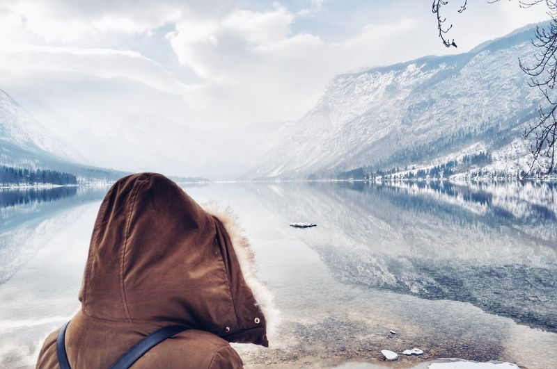 Rear view of woman by lake and snow covered mountains against sky